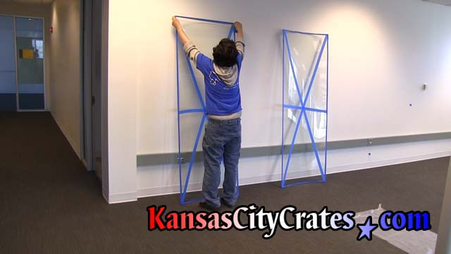 Crate builders apply blue tape to curved glass panels of revolving door