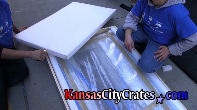 Glass panels wrapped in bubble wrap are packed with foam in commercial crate