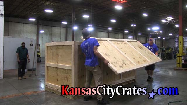 Crate builders lift lid onto industrial crate made of 2 by 4 materials and five eighths plywood on pallet base
