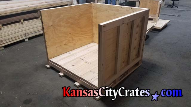 Crate builders check vault crate before steel banding onto pallet for delivery