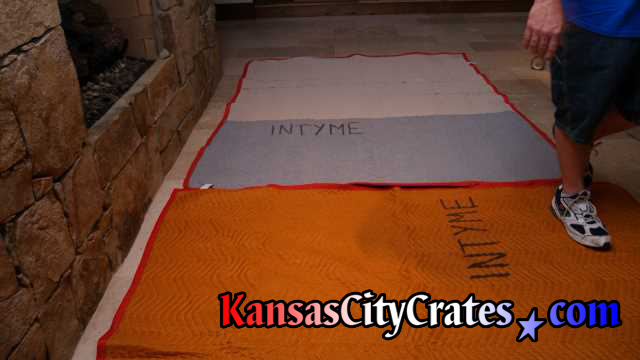Fine stone floor with furniture blankets laid out before using area to wrap items for crates.