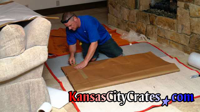 Crater working on blankets covering the floor wrapping lithograph in paper pads.
