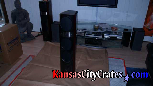 Focal speaker being wrapped in paper while sitting on furniture blanket protecting floor.