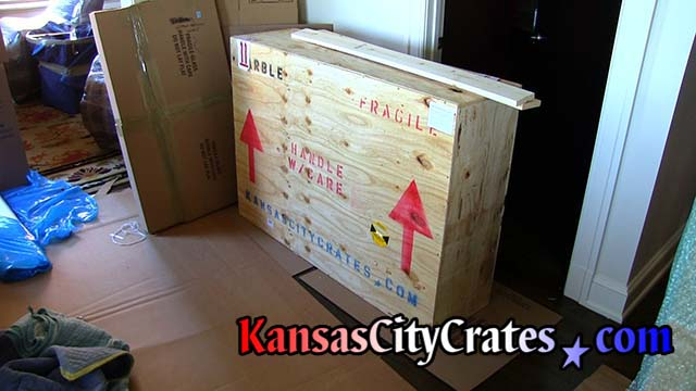 Crate with shock sensor and shipping symbols sit on cardboard to protect the floor