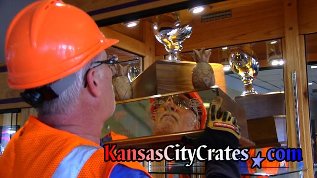 Glass cabinet holding Governor's Cup trophy opened bu crate packers wearing hard hats, gloves, eye protection, safety vests and steel toe boots