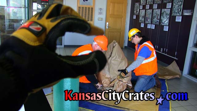 Kansas CIty Crates safety compliance officer makes funny photo with cut resistance glove by posing index finger and thumb over hard hat of project manager