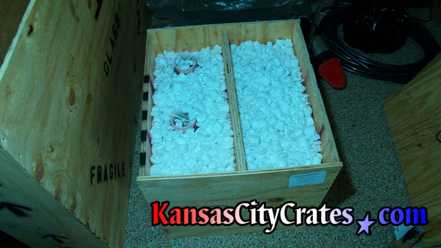 Packing peanuts protect delicate shades of sconces mounted in combo crate.