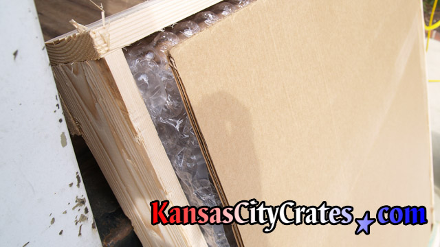 Close up view of cardboard and bubble wrap protecting picture in domestic slat crate.