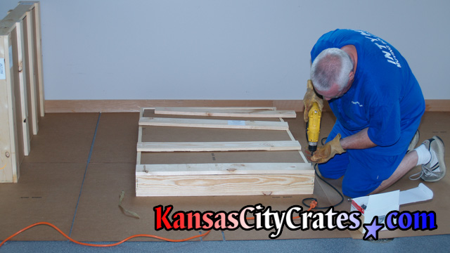 Crate builder closing crate with screws with flooring protection at home in Blue Springs MO  64015