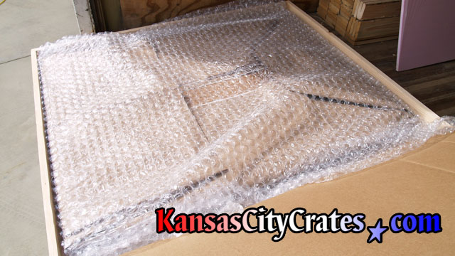 large bubble wrap used to cushion family portrait wrapped with paper at home in Roeland Park KS  66202