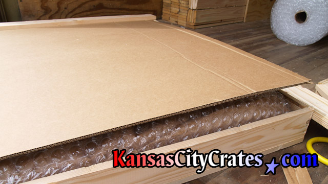 Cardboard placed over bubble wrapped artwork from office in Overland Park KS  66207