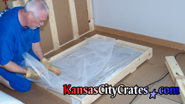 Additional bubble wrap is added for cushioning in domestic slat crate.