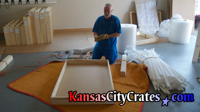 John preparing domestic slat crate on blanket in garage