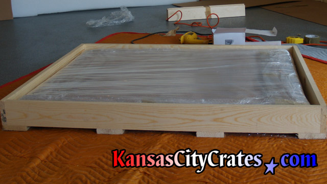 Artwork print wrapped and placed inside domestic slat crate before adding protective carboard and slats on top side.