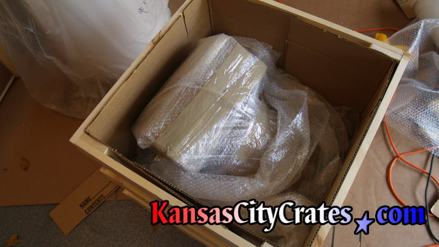 Delicate artwork in bubble wrapped has additional packing inside domestic slat crate.