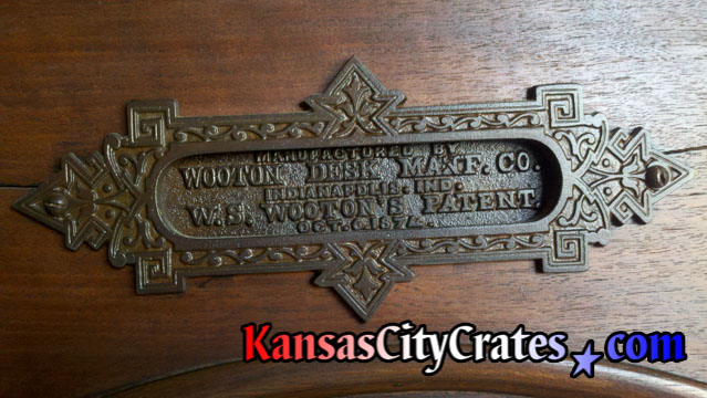 Close up photo of real solid bronze name plaque hardware on Wooton Cabinet Office Secretary desk. circa 1874