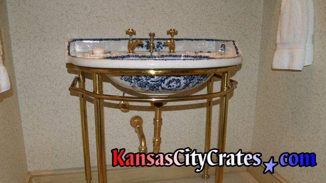 Porcelain lavatory basin with gold fixtures before crating.