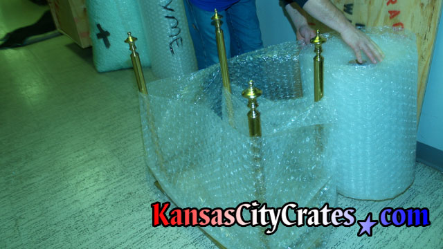 Wrapping antique brass lavatory sink pedestal with bubble wrap before crate.