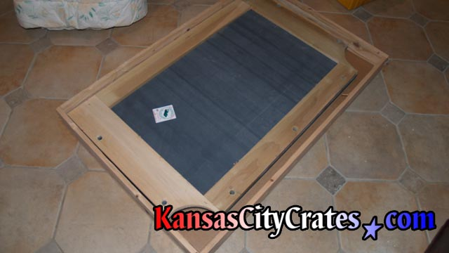 Italian slate with wood frame laying on cardboard in slat crate before packing.