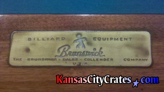 Antique name plate of the Brunswick-Balke-Collender Company at head of billiard table on rail.