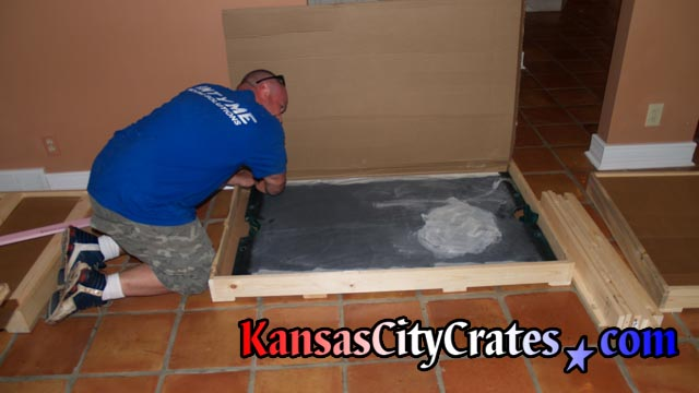 Positioning slate in crate before placing foam to protect corners.
