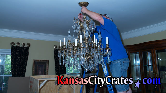 Electrician removing canopy of chandelier to disconnect wiring at home in Leawood KS 66224
