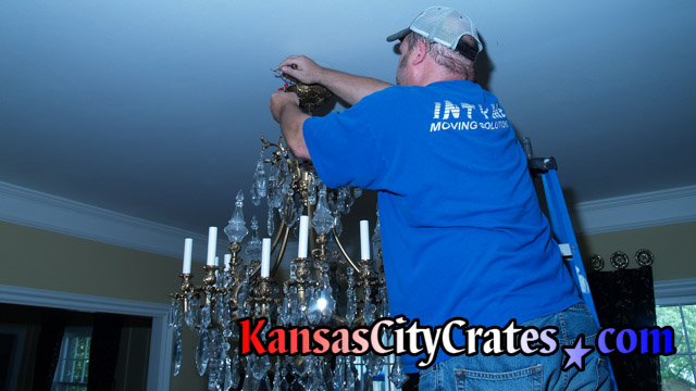 Electrician removing wire nuts under canopy of chandelier  before lowering into crate.