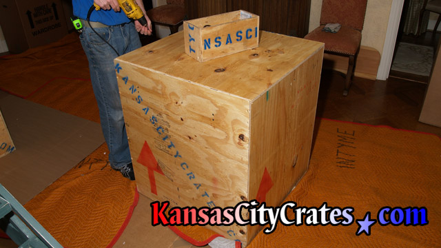 Solid wall export crate containing chandelier on flooring protection at home in Lexington MO 64067