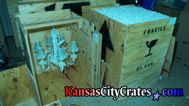 Two crates with fine porcelin chandeliers packed with foam peanuts for moving.