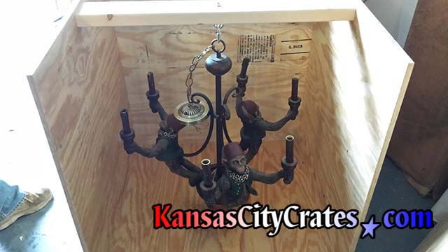 Chandelier removed from ceiling and haging on suspension hook in crate