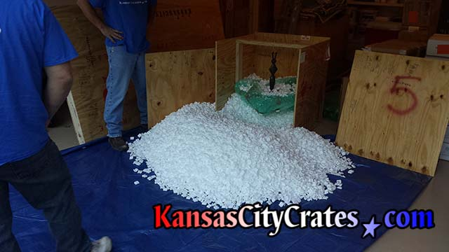 Crate is opened on large tarp to capture all the foam packing peanuts