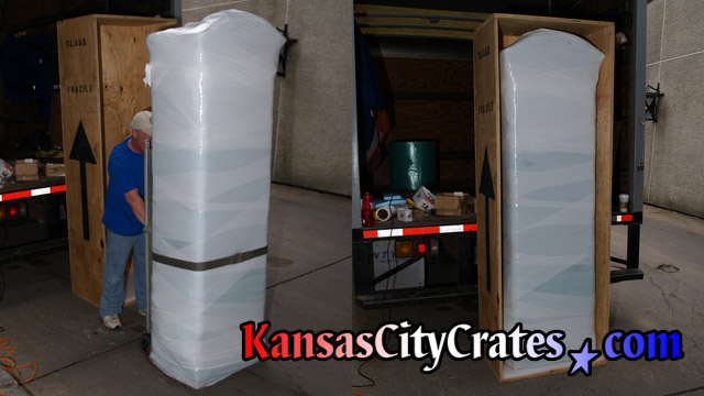 Large grandfather clock case that is paper, bubble and stretch wrapped loading into solid wall export crate for shipping at company truck.