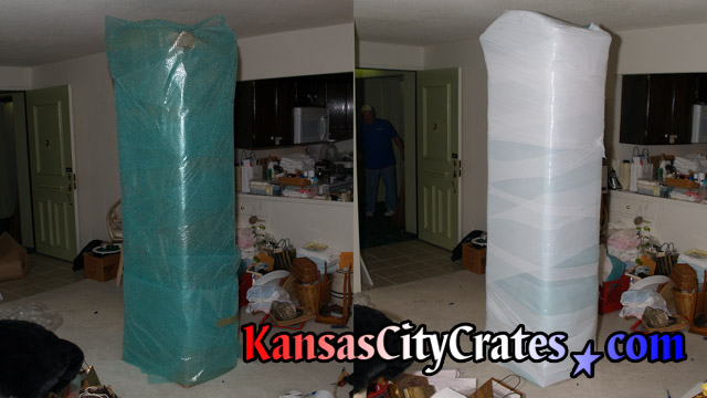 Two views of grandfather clock cabinet wrapped in bubble wrap and stretch wrap for packing into export crate for shipping.
