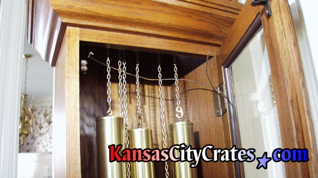 Security wire ran through chains holding clock weights before servicing movement to pack longcase cabinet into wood crate at home in Bonner Springs KS  66012