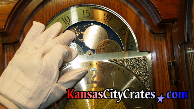 White gloves are used when touching brass parts of clock during crate company service.