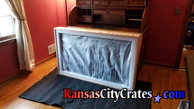 Anti-static screen protector placed over TV inside crate