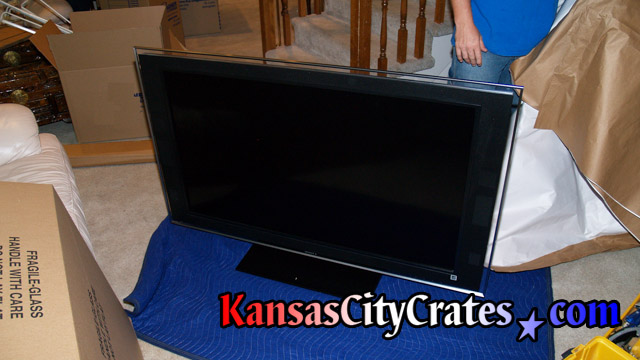 LCD Flat panel TV on blanket getting wrapped in paper pad before placing in crate.