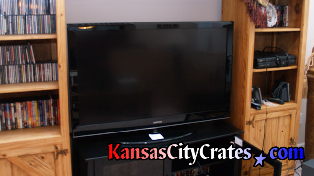Large flat panel TV sitting in entertainment center before crating.