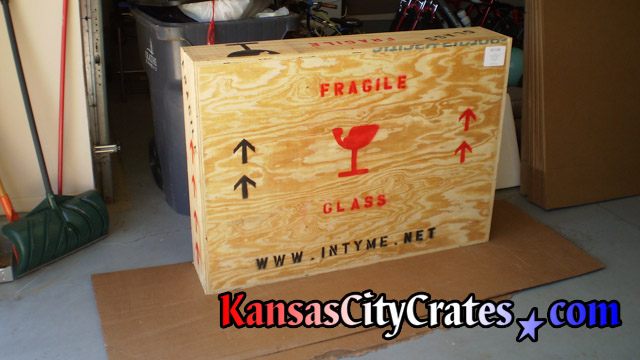 Crate marked for transport staged on carboard for loading by mover.