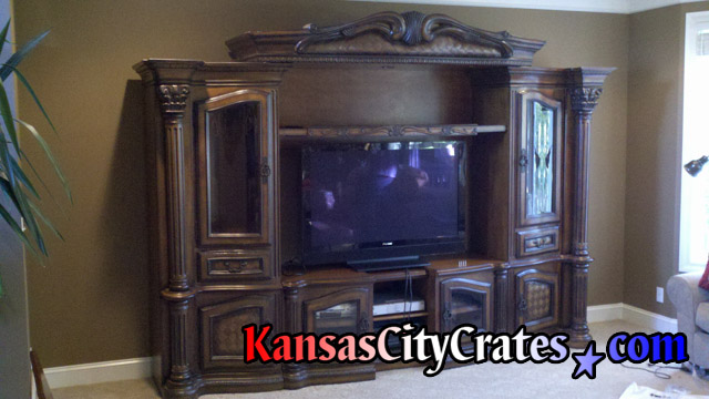 Plasma TV in older entertainment center being removed for crate.