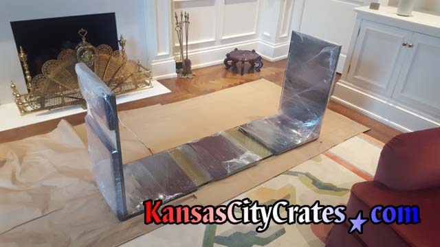 Fragile glass table is protected with foam padding secured by stretch wrap before loading into solid wall furniture crate