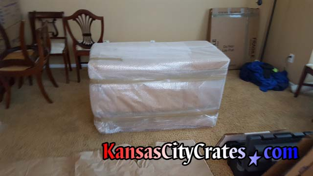 Antique drop leaf table is wrapped in paper and bubble wrap before placing into solid wall furniture crate