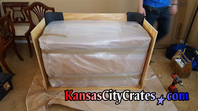 Foam corners protect antique drop leaf table inside solid wall vault like furniture crate