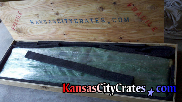 Curved glass top bubble wrapped and shrink wrapped in export crate for international shipping at Kansas City home.