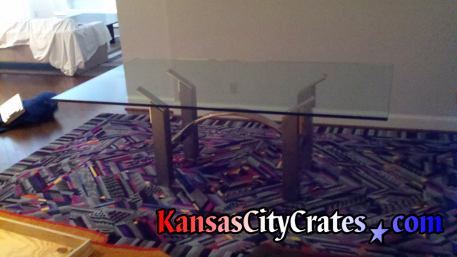 Large heavy dining room glass table top next to solid wall crate for shipping.