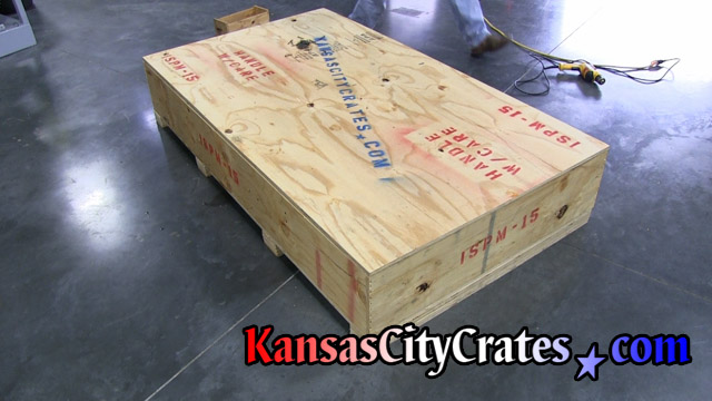 Crate with injection molding piece inside resting on cushioning.