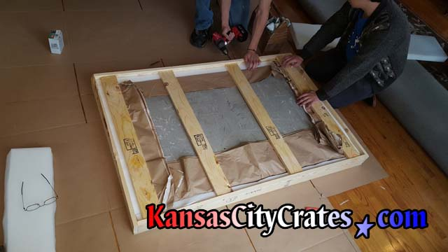Wood slats are placed inside solid wall crate to hold stone top and shipping foam in place