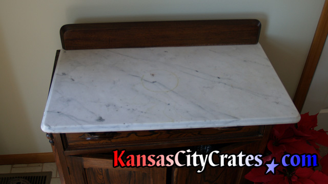 Marble top on antique furniture base before packing and crating.