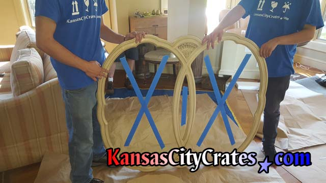 Crate builders remove antique dresser mirror and apply blue tape to glass to help reduce vibration during transport