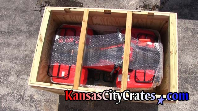 ATV in crate protected by lid supports enabling crates to be stacked during transport